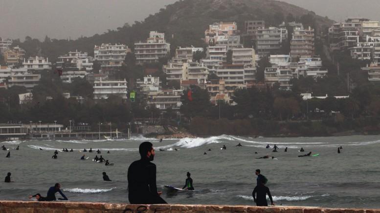 Σέρφερς παίζουν με τα κύματα που έχουν δημιουργηθεί από τους θυελλώδεις νοτιάδες σε παραλία της ...Βρωμολίμνης. Φωτό: ΑΠΕ-ΜΠΕ/ ΣΥΜΕΛΑ ΠΑΝΤΖΑΡΤΖΗ