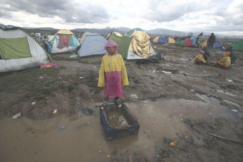 Πρόσφυγες κάθονται μέσα στις λάσπες μετά από βροχή στον καταυλισμό προσφύγων της Ειδομένης, την Παρασκευή 4 Μαρτίου 2016, περιμένοντας να πάρουν την άδεια να περάσουν από τα σύνορα της Ελλάδος προς την ΠΓΔΜ. Περισσότεροι από 13.000 μετανάστες και πρόσφυγες έχουν συγκεντρωθεί στον καταυλισμό της Ειδομένης.
