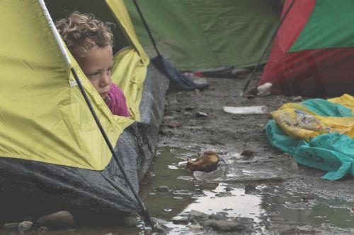 Ένα προσφυγόπουλο κάθεται μέσα στη σκηνή του μετά από βροχή στον καταυλισμό προσφύγων της Ειδομένης, την Παρασκευή 4 Μαρτίου 2016, περιμένοντας να πάρουν την άδεια να περάσουν από τα σύνορα της Ελλάδος προς την ΠΓΔΜ. Περισσότεροι από 13.000 μετανάστες και πρόσφυγες έχουν συγκεντρωθεί στον καταυλισμό της Ειδομένης.