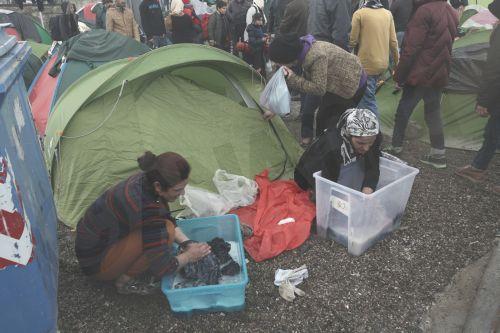 Πρόσφυγες πλένουν τα βρεγμένα ρούχα τους έξω από τη σκηνή τους μετά από βροχή στον καταυλισμό προσφύγων της Ειδομένης, την Παρασκευή 4 Μαρτίου 2016, περιμένοντας να πάρουν την άδεια να περάσουν από τα σύνορα της Ελλάδος προς την ΠΓΔΜ. Περισσότεροι από 13.000 μετανάστες και πρόσφυγες έχουν συγκεντρωθεί στον καταυλισμό της Ειδομένης.