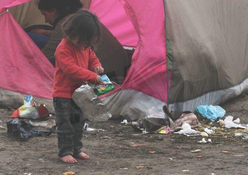 Ένα προσφυγόπουλο με γυμνά πόδια ψάχνει για φαγητό μέσα στα σκουπίδια και τις λάσπες μετά από βροχή στον καταυλισμό προσφύγων της Ειδομένης, την Παρασκευή 4 Μαρτίου 2016, περιμένοντας να πάρουν την άδεια να περάσουν από τα σύνορα της Ελλάδος προς την ΠΓΔΜ. Περισσότεροι από 13.000 μετανάστες και πρόσφυγες έχουν συγκεντρωθεί στον καταυλισμό της Ειδομένης.