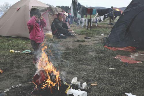 Πρόσφυγες προσπαθούν να ζεσταθούν έξω από τη σκηνή τους μετά από βροχή στον καταυλισμό προσφύγων της Ειδομένης, την Παρασκευή 4 Μαρτίου 2016, περιμένοντας να πάρουν την άδεια να περάσουν από τα σύνορα της Ελλάδος προς την ΠΓΔΜ. Περισσότεροι από 13.000 μετανάστες και πρόσφυγες έχουν συγκεντρωθεί στον καταυλισμό της Ειδομένης.