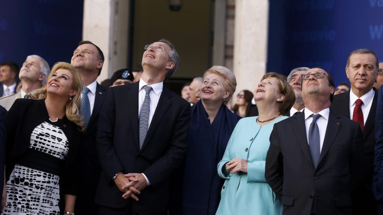 Participants react as they observe a fly past during the NATO Summit in Warsaw