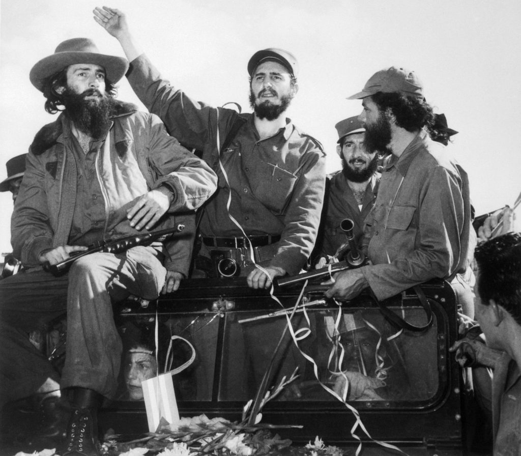 Revolutionary leader Fidel Castro waves to a cheering crowd upon his arrival in Havana, Cuba, after dictator Fulgencio Batista fled the island.